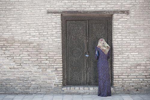 Biddende vrouw bij een stenen gebouw met een houten deur | Turkmenistan
