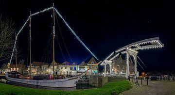Panorama foto van een verlichte zeilboot en een ophaalbrug nabij de Drommedaris von Ardi Mulder
