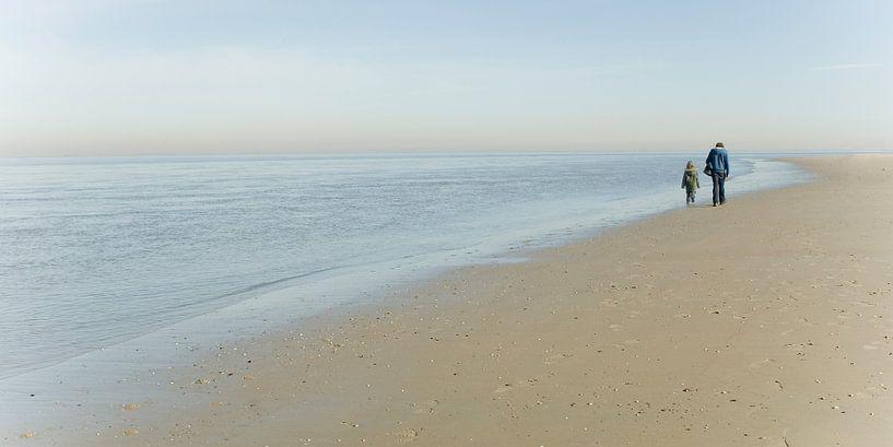 Vader en zoon lopen langs het strand van Texel van Margo Schoote