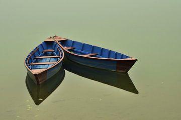 Boote auf dem goldenen Wasser. Boote sind an die Säulen des ruhigen Wassers gebunden von Michael Semenov