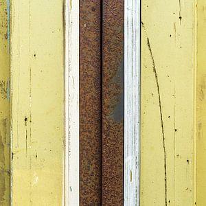 Abstract lijnenspel met hout en roestige pijp in geel en bruin van