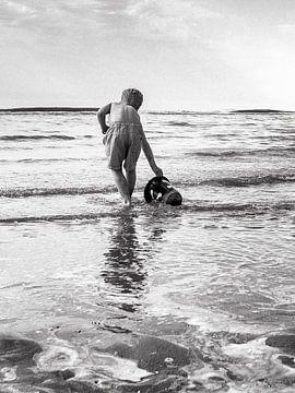 Kind spielt mit Eimer im Meer von Kim Groenendal