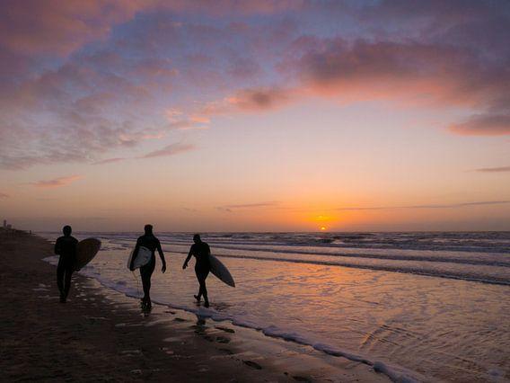 Surfers tijdens zonsondergang