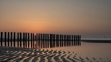 De zon zakt weg achter de golfbrekers van Bram van Broekhoven