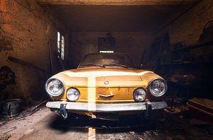 Gelber Fiat in verlassener Garage.