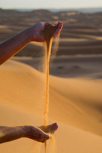Handen spelen met Sahara zand.