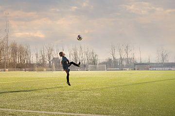 Kind probt mit dem Ball auf dem Fußballfeld von Kim Groenendal