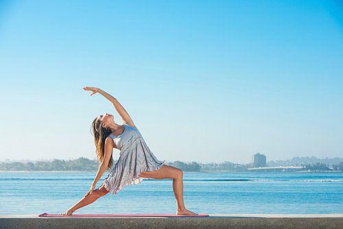 Jonge vrouw in zomerjurk beoefent yoga aan het strand