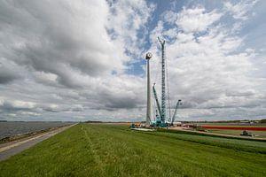 Bouw van een moderne windmolen aan de dijk in Nederland