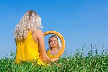 Jonge vrouw zit met spiegel in gras met blauwe lucht van Ben Schonewille