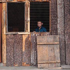 Jongen achter open raam in hut bij Thimphu Bhutan. Wout Kok One2expose van Wout Kok