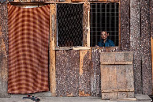 Jongen achter open raam in hut bij Thimphu Bhutan. Wout Kok One2expose van
