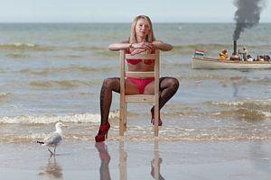 Mädchen auf Stuhl am Strand
