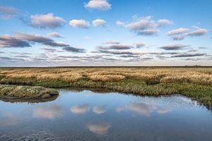 Avondlicht op het Wad Nabij Paesens Moddergat met wolken gespiegeld in stilstaand water.