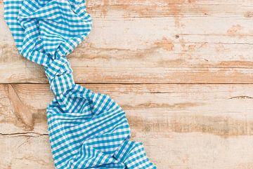 Nappe à carreaux bleus noués sur fond de table en bois rustique, vue de dessus sur Alex Winter