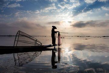 VISSER OP TRADITIONELE MANIER BIJ ZONSOPGANG AAN HET WERK OP HET van Wout Kok