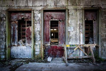 De drie rode deuren in een verlaten fabriek van