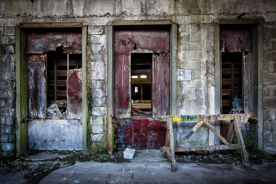 De drie rode deuren in een verlaten fabriek