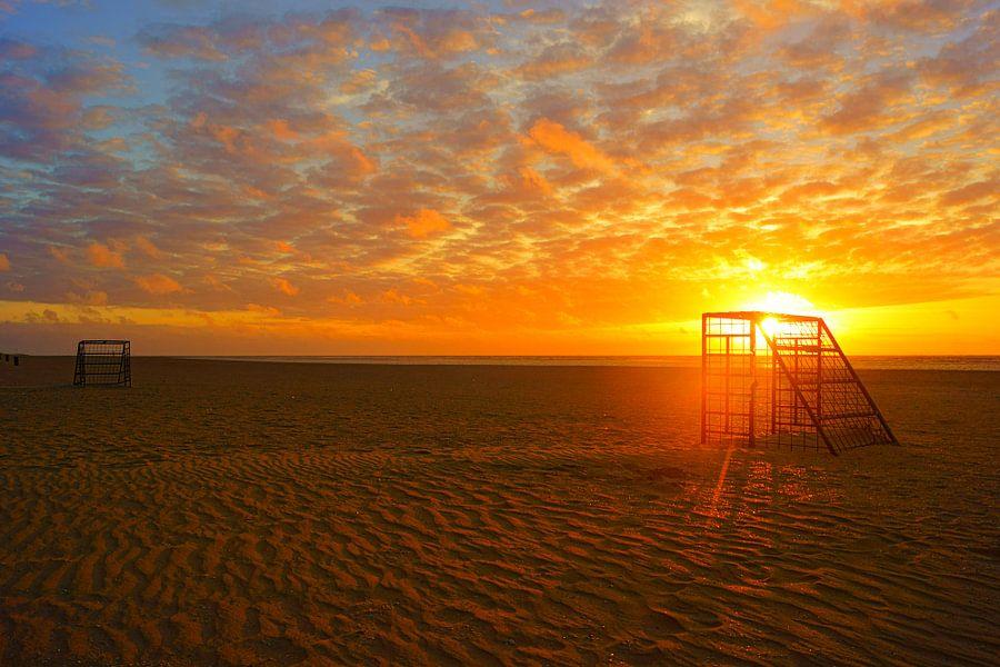 Voetbalveld bij op het strand bij zonsondergang