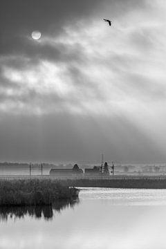 de zon schijnt door de wolken over het water en het landschap van Marc Goldman