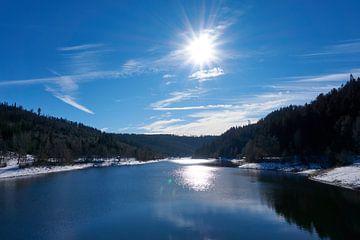 Bevroren rivier met sneeuw en ijs in zonneschijn onder blauwe hemel in Nagoldtalsperre van creativcontent