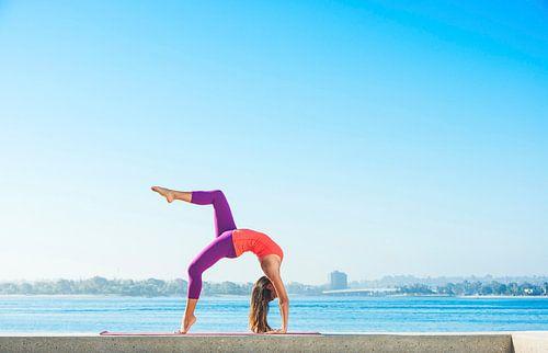 Jonge vrouw beoefent yoga op een smalle muur aan de kust van