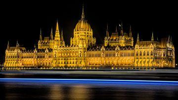 Ungarisches Parlamentsgebäude bei Nacht mit vorbeifahrendem Boot von Hannon Queiroz