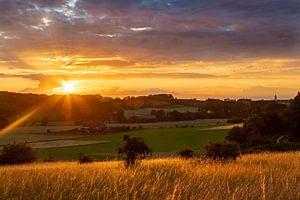 warme zonsondergang met mooie stralen en een heerlijke rood en gele gloed van Kim Willems