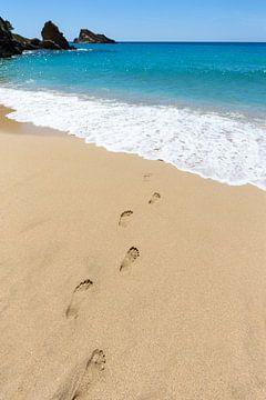 Fußspuren im Sand, die führen zu blauen Meer an der Küste auf der Insel in Griechenland von