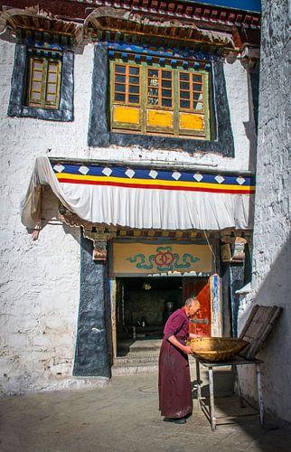 Monnik aan het werk op de binnenplaats van het klooster, Tibet