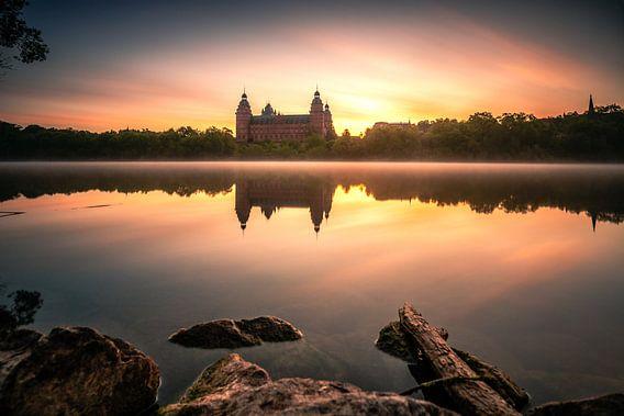 Het kasteel Johannisburg in Aschaffenburg Duitsland in de mist en de zonsopgang met reflectie