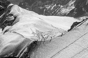 Bergsteiger auf einem Bergrücken in verschneiter Landschaft (schwarz und weiß) von Martijn Joosse