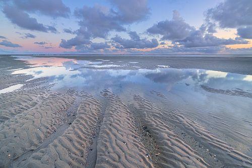 Eb op het strand van Westerschouwen op Schouwen Duivenland in Zeeland. De wolken weerspiegelen in he