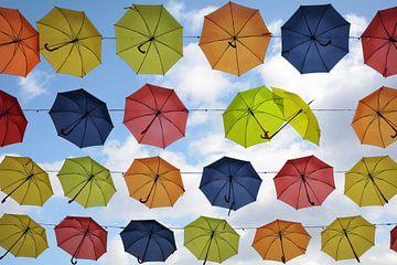 kleurrijke hangende paraplu's in de lucht, twee zijn flirten, straatdecoratie achtergrond van Maren Winter