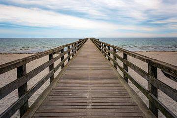 Holzsteg führt direkt über den Strand und das Meer zum Horizont, Konzept für den Weg in eine ungewis von Maren Winter