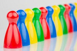 Conceptuele gekleurde speelpionnen in een rij van