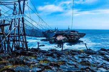 Daag uit over een slingerende touwbrug en touwbaan over sterk golvende zee naar een rotseiland. van kall3bu