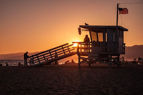 Zonsondergang met een strandwacht (Lifeguard) huisje langs de kust van Santa Monica Californië veren
