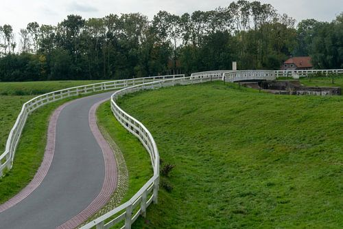 Landweg met wit hekwerk.