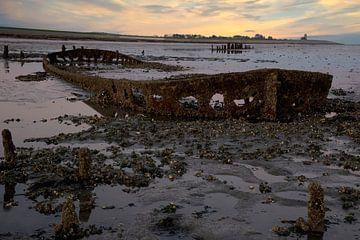 Zonsondergang aan de Waddenzee met een scheepswrak van Gert Hilbink