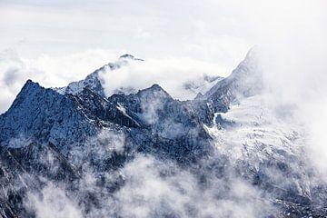 Hoge bergtoppen in de alpen omringd door wolken van Hidde Hageman