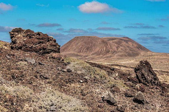 Landschap Lanzarote met lava rotsblokken op de voorgrond.