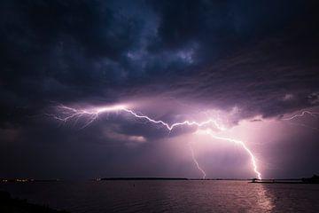 Bliksem in de donkere nachtelijke hemel boven een meer in de zomer van Sjoerd van der Wal