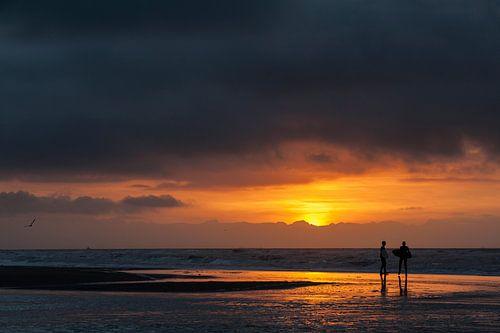 Surfers - zonsondergang van Dick van Duijn