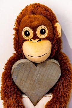 Ein Stoff Affe hängt an einem Herz aus Holz von Tom Voelz
