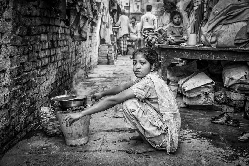 Meisje doet de was  in achterbuurt van Varanasi in India van Wout Kok