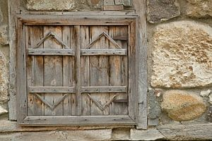 Old wooden shutters in a stone wall.