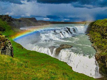 Bedrohlich Himmel mit Regenbogen über dem Goldenen Wasserfall, Island von Rietje Bulthuis