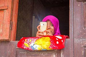 Lombok, Indonesie: Jong en ondeugend meisje met haar mobiele telefoon van
