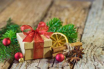 Kerstcadeau met rood lint en natuurlijke versieringen op houten achtergrond van Alex Winter